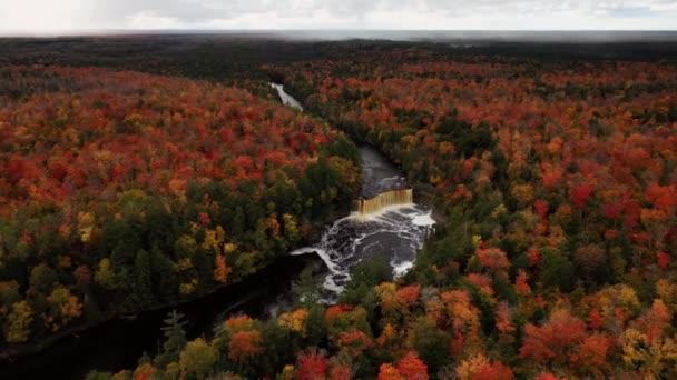 Krásné pánve ve vzduchu přeletět Tahquamenon vodopád klesá směrem ke kaskádě a řece obklopen krajinou stálezeleně a barevné opadavé strom podzimní listí.