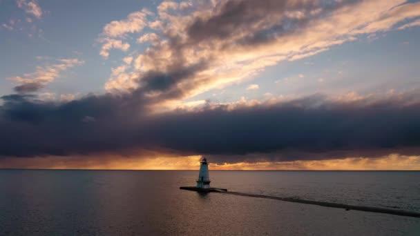 Schöne Sonnenuntergang Antenne schwebt vor dem weißen Leuchtturm Ludington Wellenbrecher mit blauem und orangefarbenem Himmel und Wolken über reflektieren das Wasser des Lake Michigan.