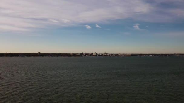 Panoramaflug über das ruhige Wasser des Eriesees in Richtung Sandusky, Ohios Stadtsilhouette entlang der Küste der Großen Seen, während unten Schwärme kanadischer Gänse fliegen.