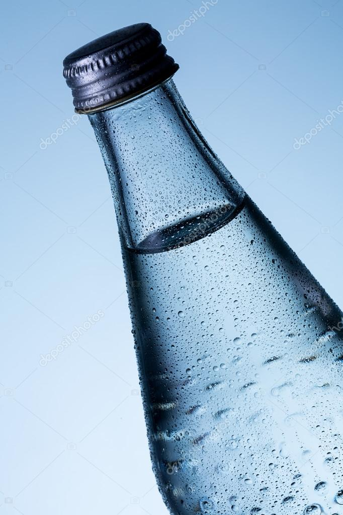 Glass bottle of water with dew drops