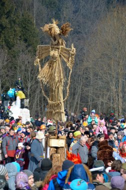 Abramtsevo, Moscow region, Russia, March, 13. 2016. People taking part in celebration of Bakshevskaya Shrovetide near straw effigy of Maslenitsa