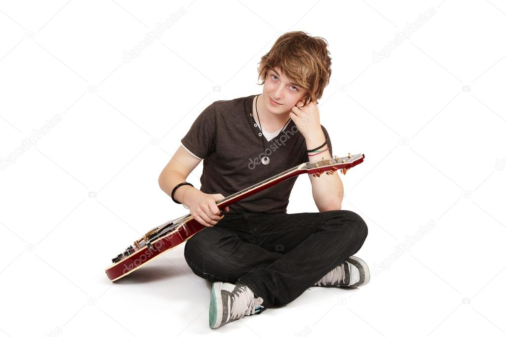 Young guitarist sitting crossed legs