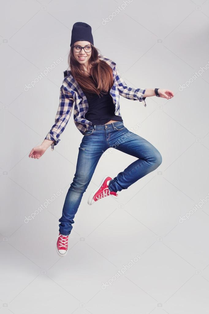 3961d22c28f Dancing hipster girl in glasses and black beanie on the wooden background —  Photo by ...