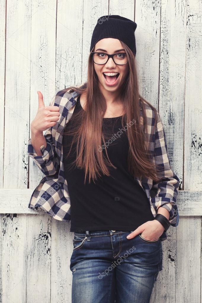 Fille de hipster à lunettes et bonnet noir avec les pouces vers le haut sur  le fond en bois \u2014 Image de doodko