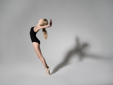 Ballerina in black outfit posing on toes