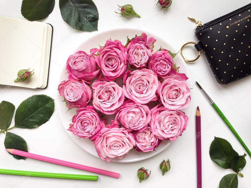 Colorful composition with sketchbook, roses and accessories. Flat lay