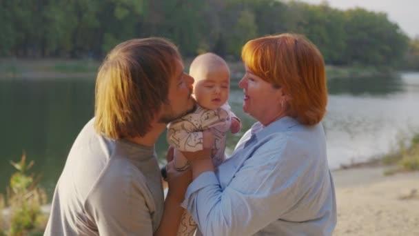 A nagymama kint tartja a kisbabát a karjában. Nagyszülő kötődés unokával.