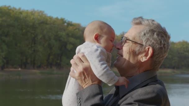 Lustiges Spiel und Lachen des kaukasischen Alten und kleinen Mädchens in häuslicher Gemütlichkeit. Faltige Haut des Großvaters oder grauhaarigen Vaters. Sanfte Umarmung und glückliches Lächeln Großeltern.