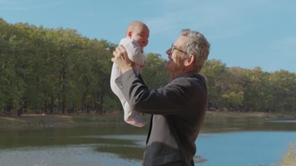 Älterer Mann spricht mit seinem kleinen Enkel, hält ihn in der Luft, Nahaufnahme, Seitenansicht.