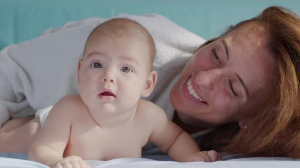 Happy mother and her newborn baby. Resting in bed together. Maternity concept. Parenthood. Motherhood Beautiful Happy Family Slow Motion.