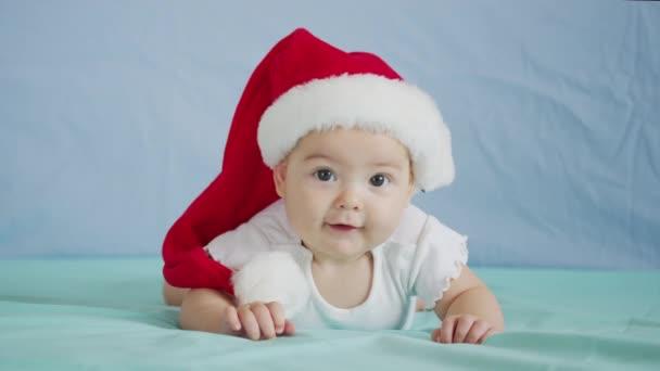 Veselé Vánoce a šťastný nový rok, dětství, dovolená koncept close-up. 3 měsíce staré novorozeně v Santa Claus klobouk na břiše plazí.