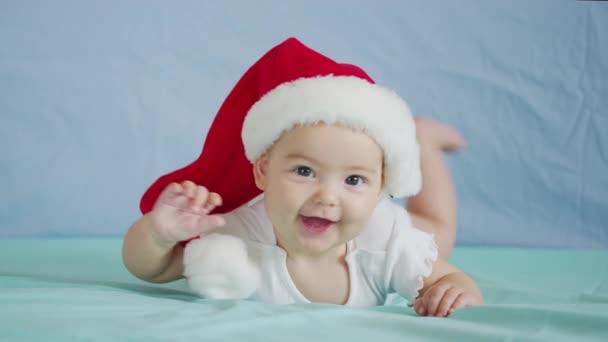 Portrét rozkošné malé holčičky v Santově klobouku. Koncept Vánoční oslavy.