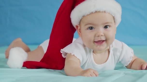 Frohe Weihnachten und einen guten Rutsch ins neue Jahr, Kindheit, Urlaub aus nächster Nähe. 3 Monate altes Neugeborenes in Nikolausmütze auf dem Bauch kriecht.