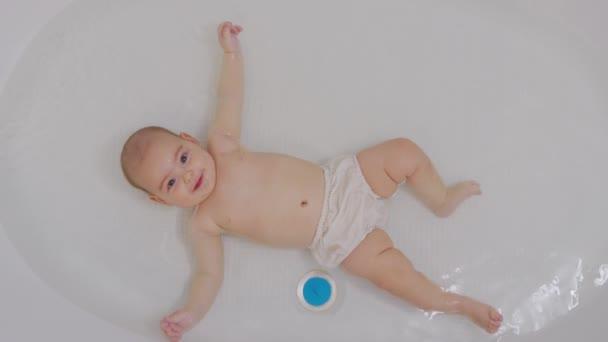 Glückliches Babybaden. Fröhliches fünf Monate altes Kind im Wasser.