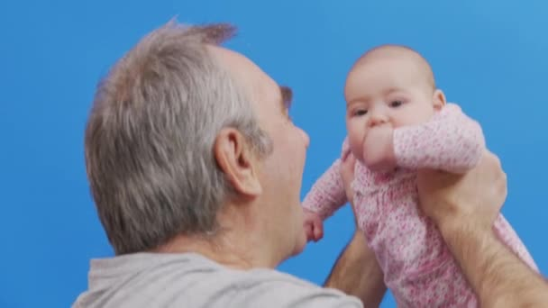 Älterer Mann im Gespräch mit seiner kleinen Enkelin, hält sie in der Luft, Nahaufnahme, Seitenansicht. Vereinzelt auf blauem Hintergrund.