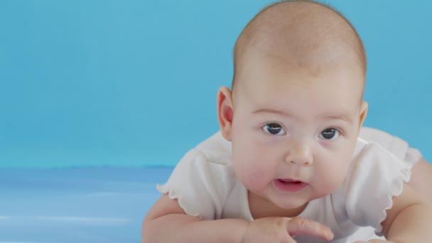 Nahaufnahme Porträt eines kleinen Mädchens. Das Gesicht eines kleinen kaukasischen Mädchens, das auf dem Bett liegt. Baby 6 in die Kamera schauen.