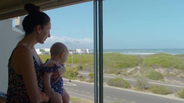 Mutter hält Baby in der Nähe eines Fensters, das dem Kind das Meer zeigt.