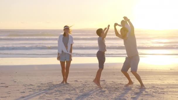 Happy family playing and having fun on the beach at sunset. Slow Motion. Family, Freedom and Travel concept.