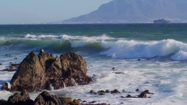 Scenic kilátás hullámok Atlanti-óceán Fokváros, Dél-AfrikaTable Mountain a háttérben egy hajó a távolban.