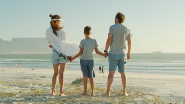 Happy family walks in the beach in the sun at sunset. Mom, dad and babys happy walk at sunset. Joint family walks healthy lifestyle. The concept of a happy family and family values.