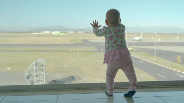 Little baby girl looks out of window at airport. Child looking at the plane through the window at waiting hall.