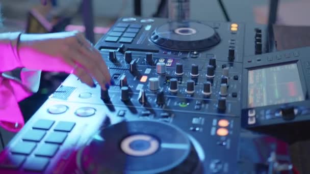 Close up. DJ sound control console for mixing dance music in disco club. Hands touching buttons sliders, playing electronic music on mixing deck, color illumination in nightclub dance party.