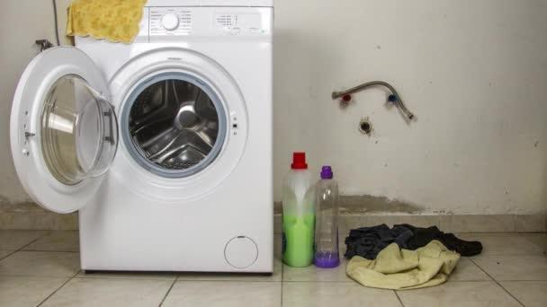 Zeitraffer stoppt, dass die Waschmaschine mit Kleidung gefüllt wird