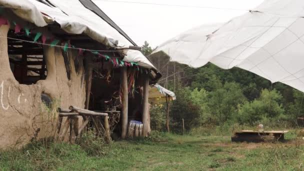 Ecovillage settlement in Yushki, Ukraine. Dřevěný hliněný dům s bílým padákem stan natažený v blízkosti