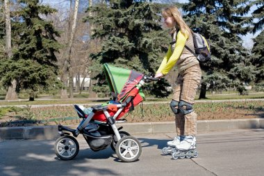 Young mother on roller skates with baby carriage