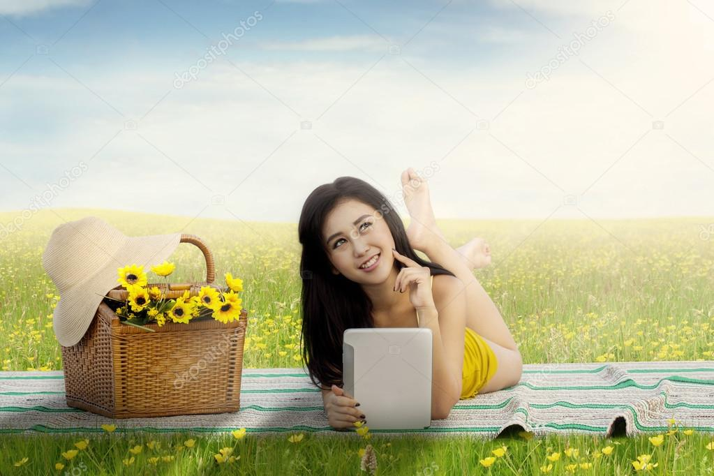 Pretty girl with tablet picnic on meadow