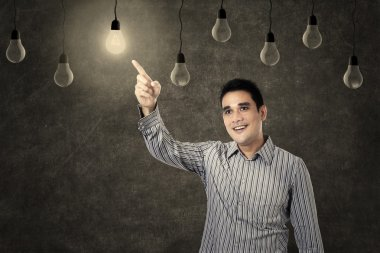 Smiling man pointing at lit bulb