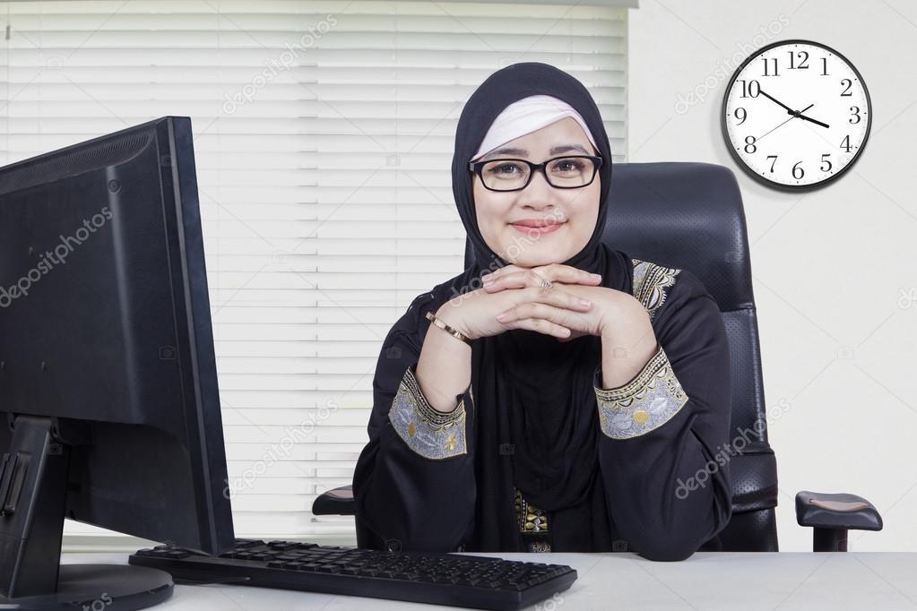 Jolie arabe femme souriant au bureau u photographie realinemedia