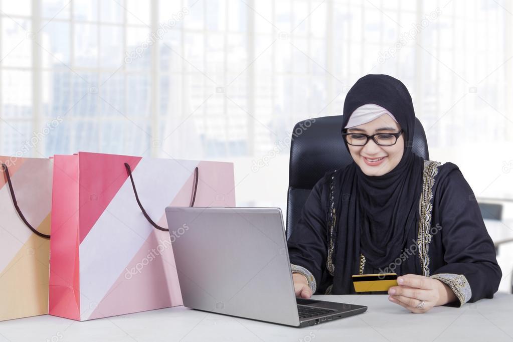 Arabe travailleuse magasinage en ligne au bureau u photographie