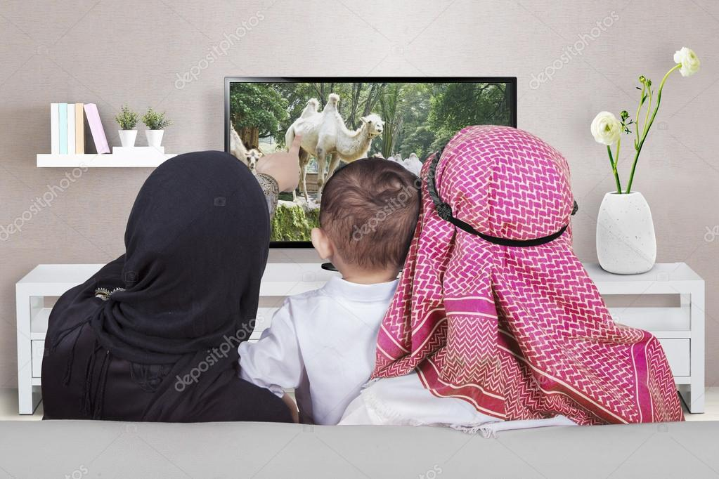 Arabic family watching television at home — Stock Photo ...