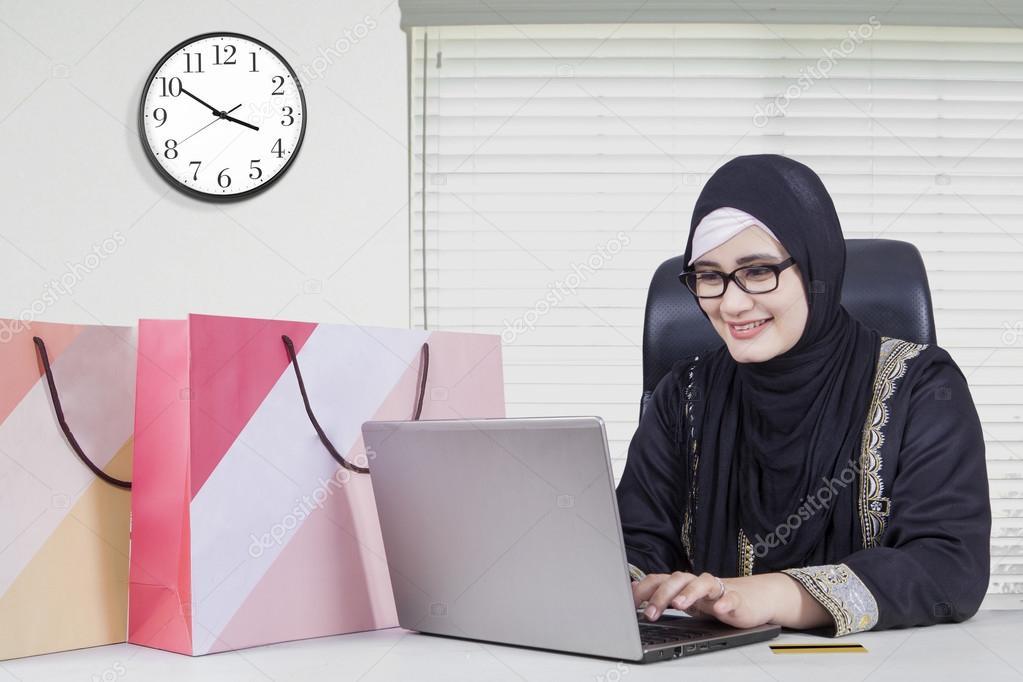 Jolie arabe femme shopping en ligne au bureau u photographie