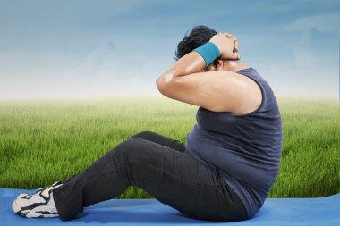 Fat man workout on mattress outdoors
