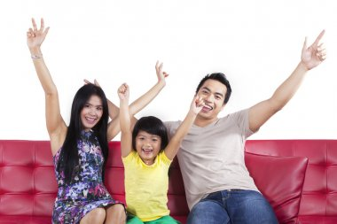 Cheerful family sitting on sofa isolated