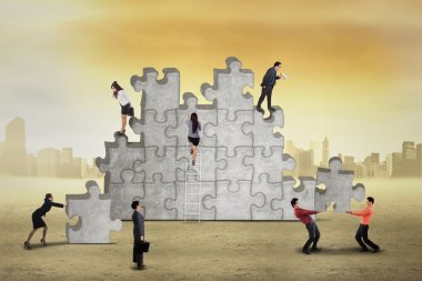 Busy businesspeople arrange puzzle