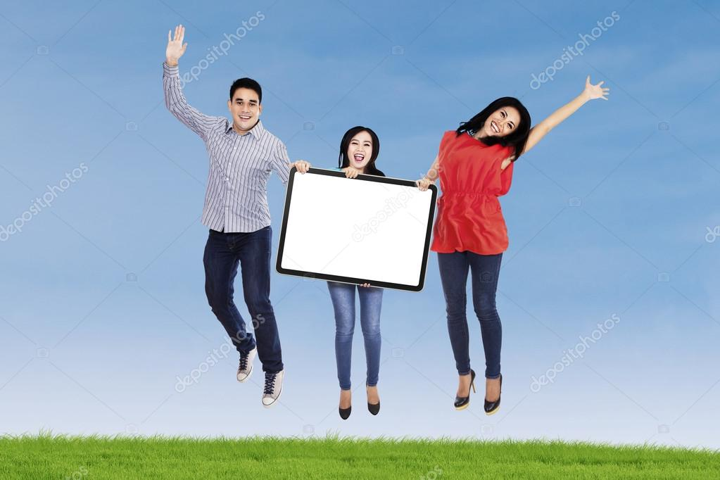 Happy people jumping with blank board