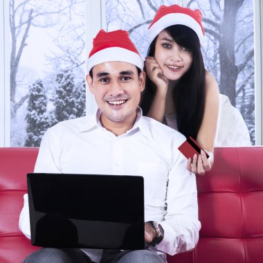 Smiling couple in santa hat paying online