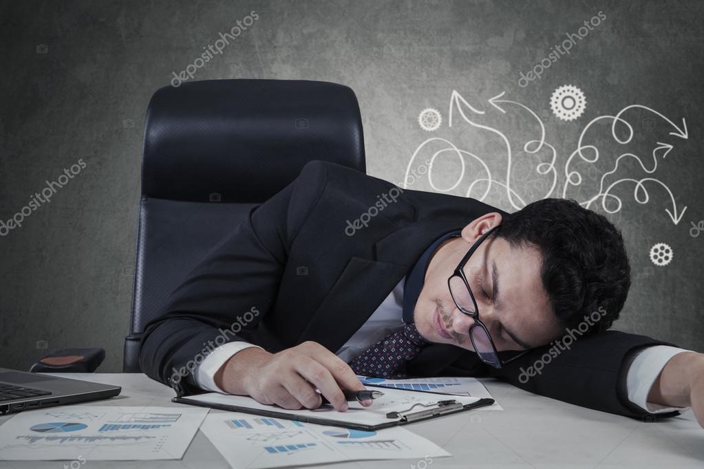 Gestionnaire confus de dormir sur le bureau u photographie