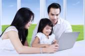 Mädchen von ihren Eltern beim Lernen unterstützt