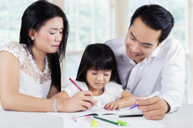 Child studying with parents in home