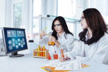 Two schoolgirls doing research in lab