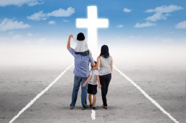 Young family follow a cross on the road