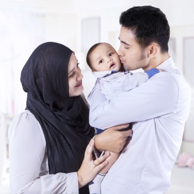 Happy muslim family standing in the bedroom