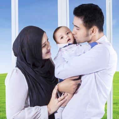 Parents kiss their baby near the window