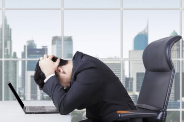 Hopeless worker working with laptop in office