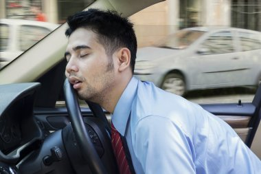 Tired young man sleeping inside the car