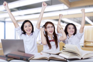 Three happy students raise hands in class